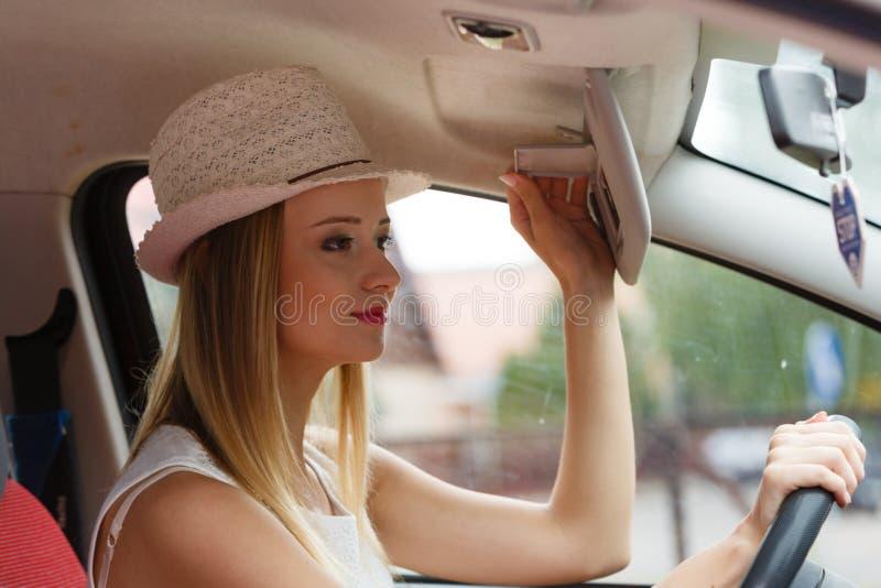 Mujer distraída que conduce su coche que mira en espejo imagenes de archivo