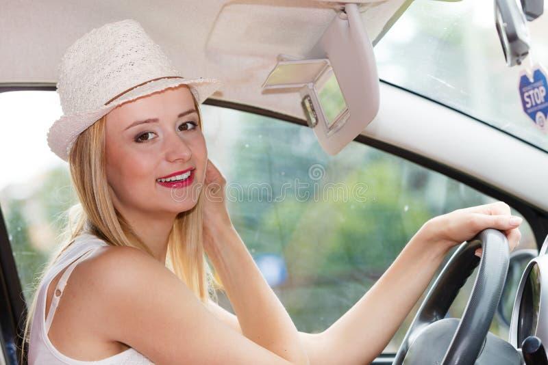 Mujer distraída que conduce su coche que mira en espejo imagen de archivo libre de regalías