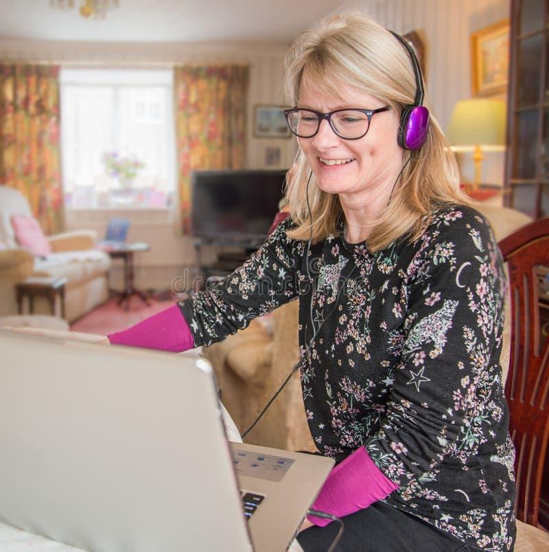 Mujer divertida con el ordenador portátil, mirando el contenido divertido imagen de archivo libre de regalías