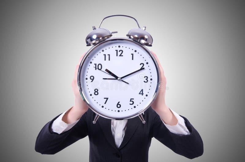 Mujer divertida con el reloj en el blanco imagen de archivo