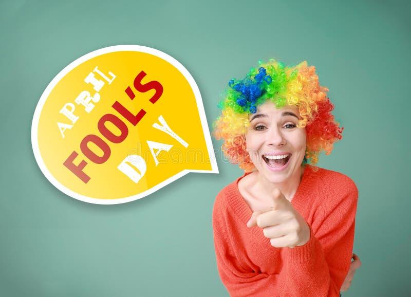 Mujer divertida con la peluca para la celebración del día de los inocentes en fondo del color imagen de archivo