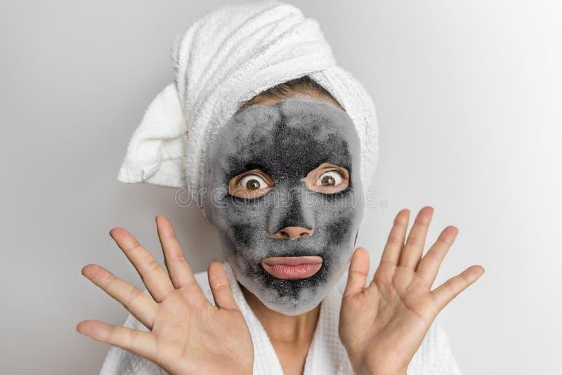 Mujer divertida facial de la espuma de la burbuja de la mascarilla en el balneario de la belleza que mira sustancias químicas cho fotografía de archivo libre de regalías