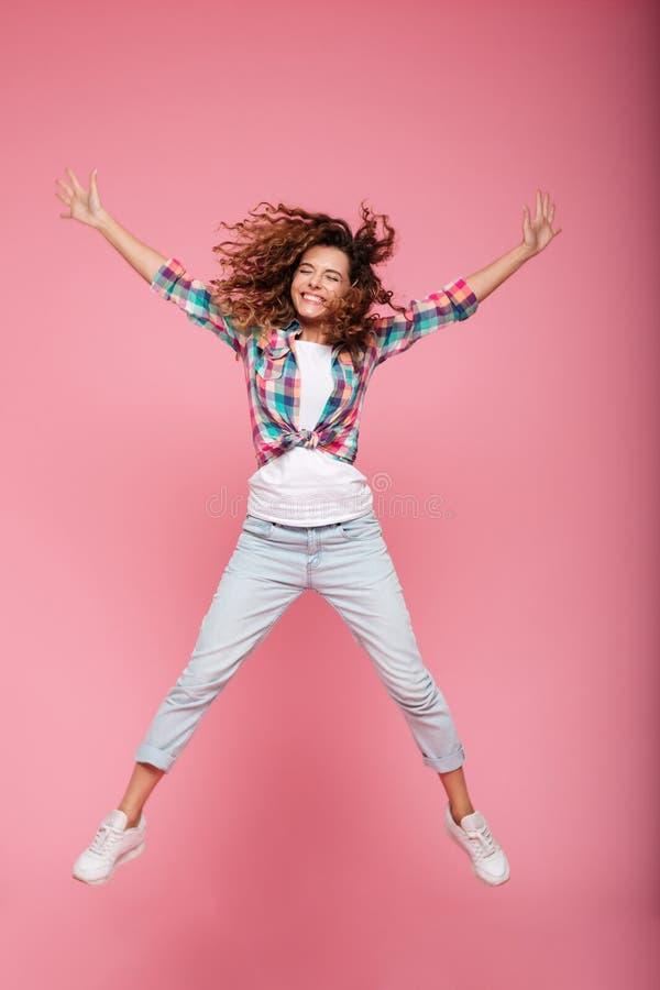 Mujer divertida feliz joven en el salto de la ropa casual aislada fotos de archivo