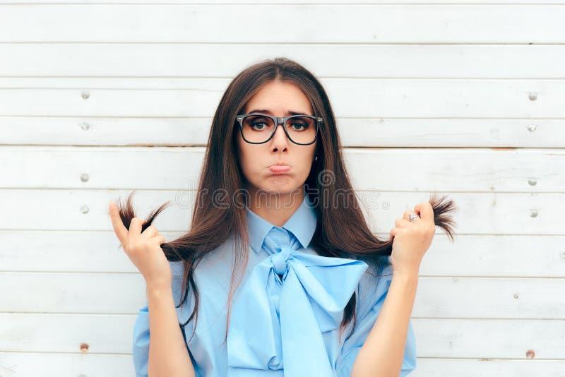 Mujer divertida que comprueba su pelo para saber si hay extremos partidos fotos de archivo