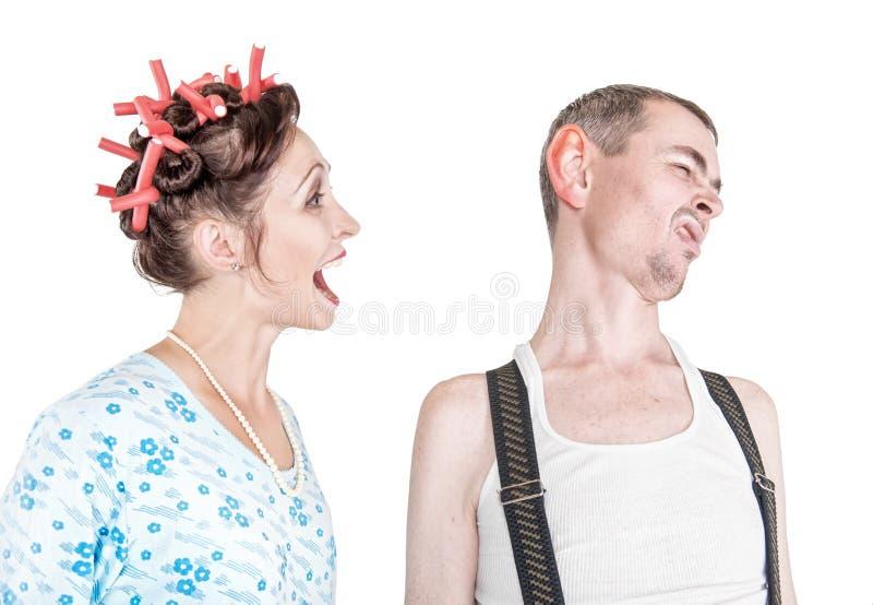 Mujer divertida que grita en su marido con el oído grande fotos de archivo