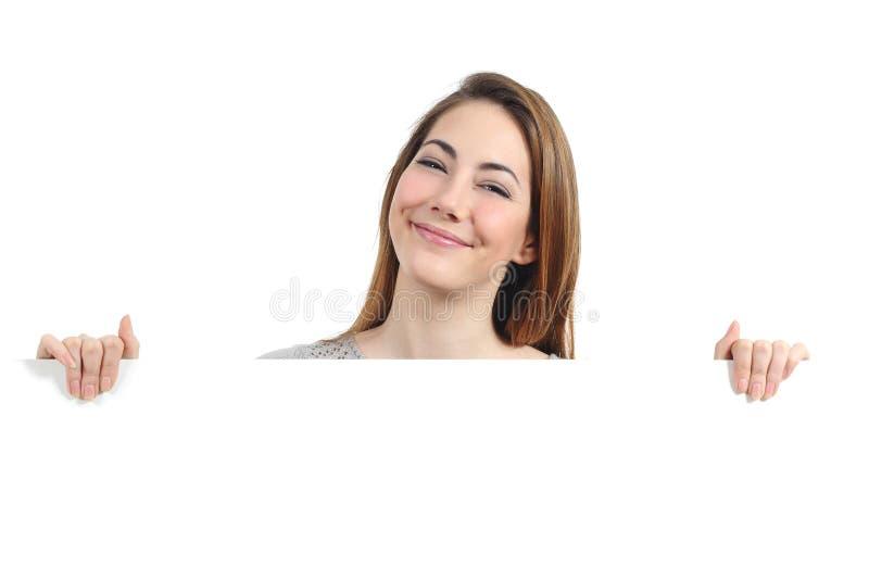 Mujer divertida que presenta y que lleva a cabo una muestra en blanco foto de archivo