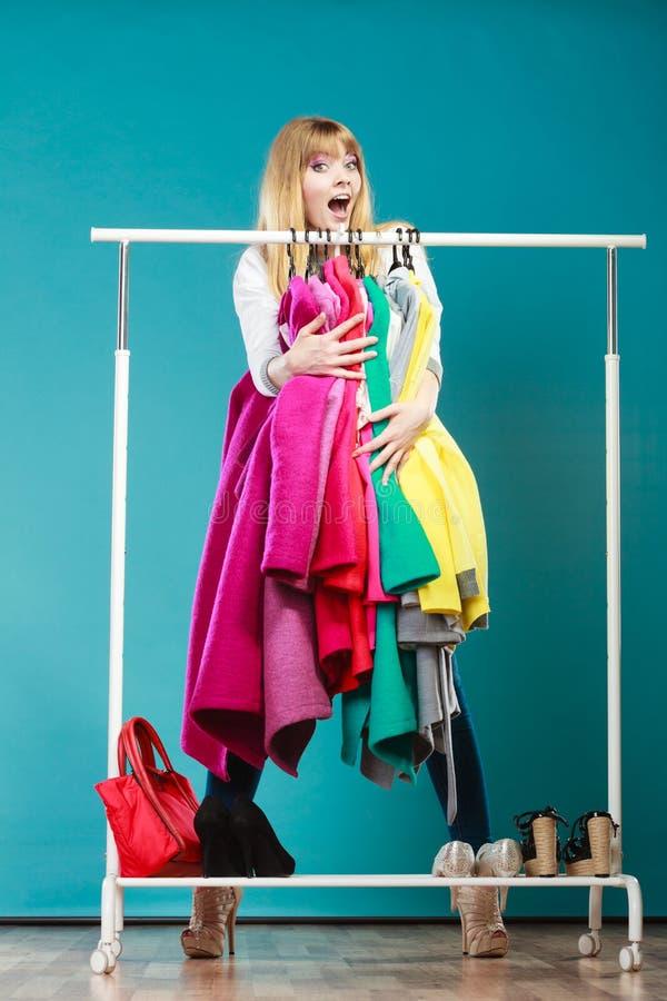 Mujer divertida que toma toda la ropa en alameda o guardarropa imagen de archivo libre de regalías