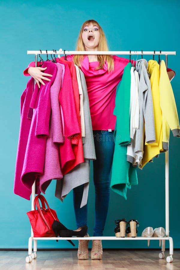 Mujer divertida que toma toda la ropa en alameda o guardarropa foto de archivo