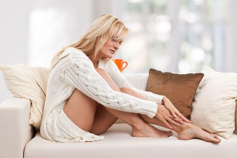 Mujer dolorosa del blondie en el sofá imagen de archivo