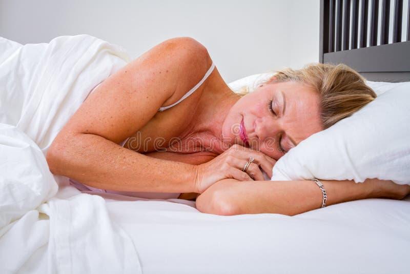 Mujer dormida en cama fotografía de archivo