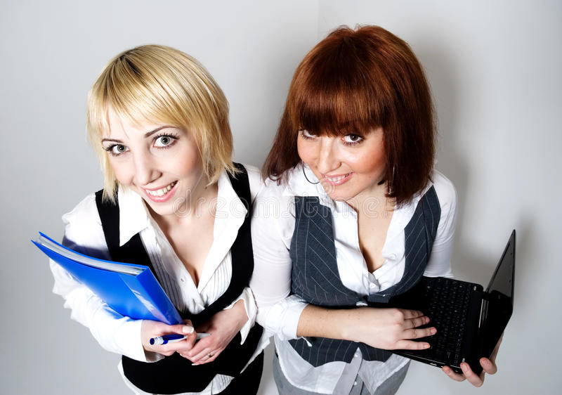 Mujer dos con la carpeta y la computadora portátil imagenes de archivo