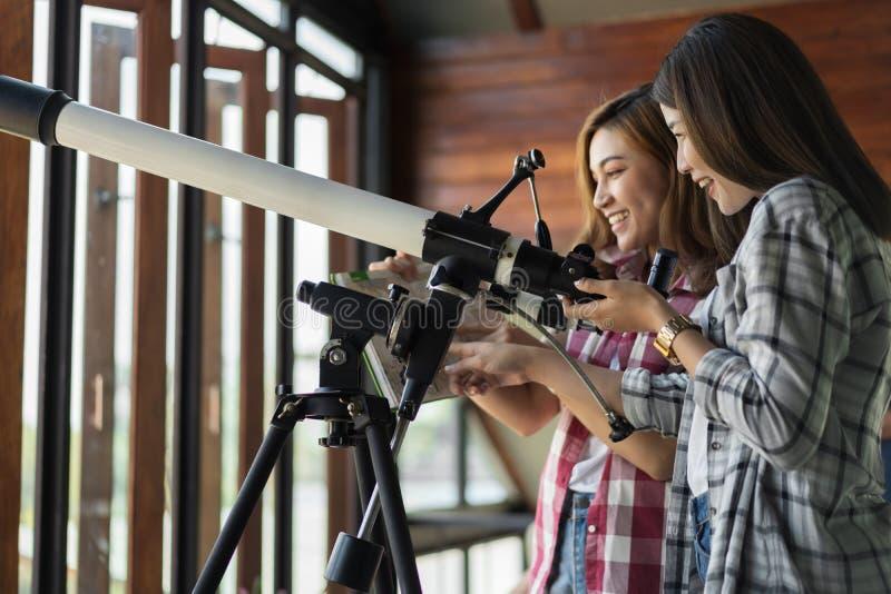 Mujer dos que mira a través del telescopio fotos de archivo
