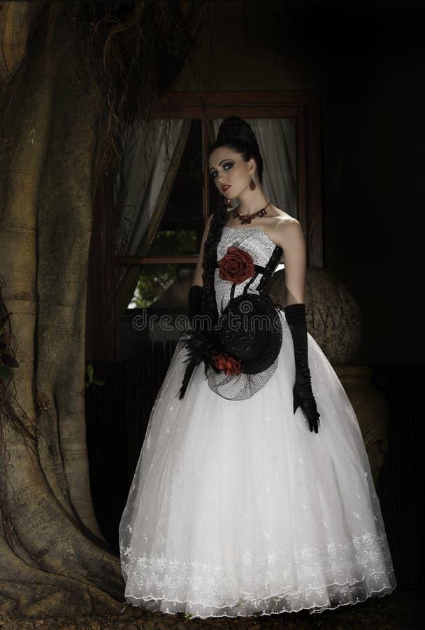 Mujer dramática en costuras rojas, blancas y negras fotos de archivo