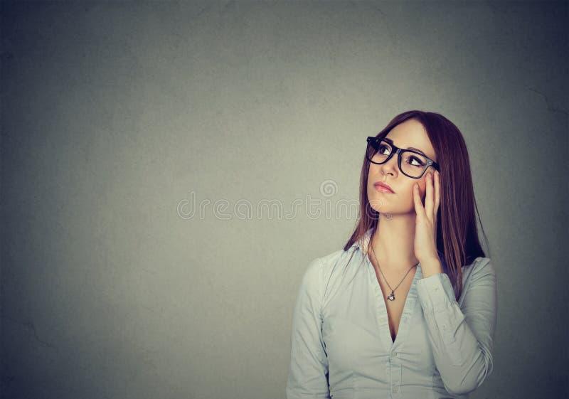 Mujer dudosa que mira para arriba en maravillas fotos de archivo