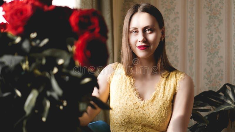 Mujer dulce rom?ntica agradable con el ramo de rosas rojas en el apartamento interior beige imagenes de archivo