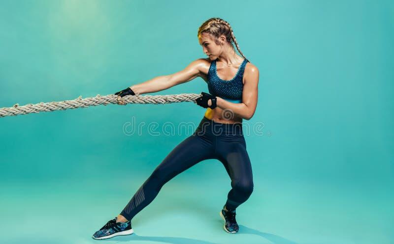 Mujer dura de los deportes que ejercita con la cuerda de lucha imagenes de archivo