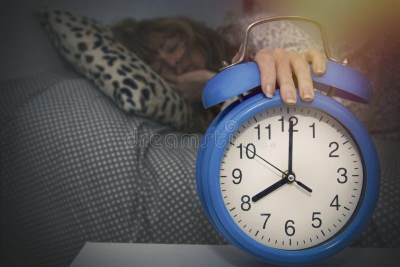 Mujer durmiendo con la mano en la alarma foto de archivo libre de regalías
