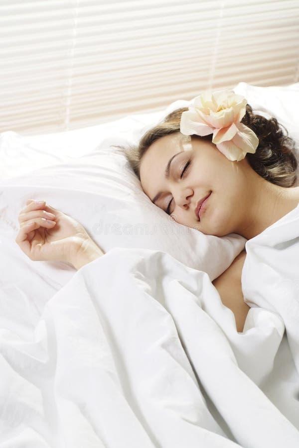 Mujer durmiente por la mañana en cama   fotografía de archivo