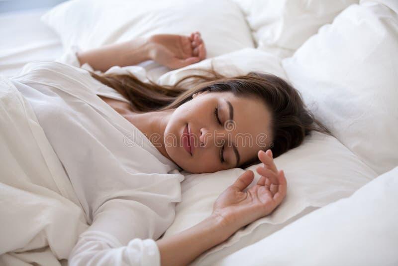 Mujer durmiente que disfruta de resto en cama acogedora por la mañana imagenes de archivo