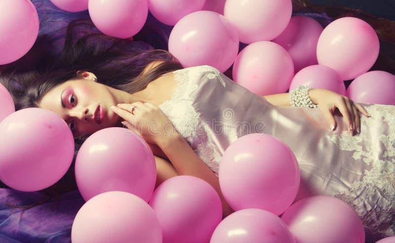 Mujer durmiente que miente en piso entre los globos imágenes de archivo libres de regalías