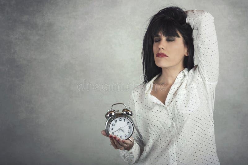 Mujer durmiente que sostiene el reloj imagen de archivo