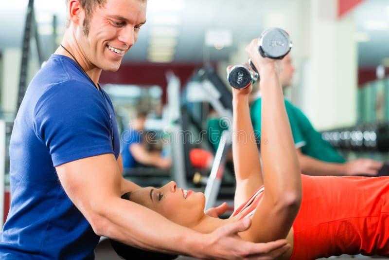 Mujer e instructor personal en gimnasio, con pesas de gimnasia fotos de archivo