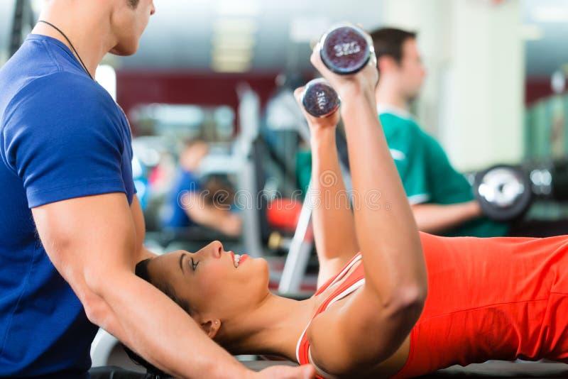 Mujer e instructor personal en gimnasio, con pesas de gimnasia imagen de archivo libre de regalías