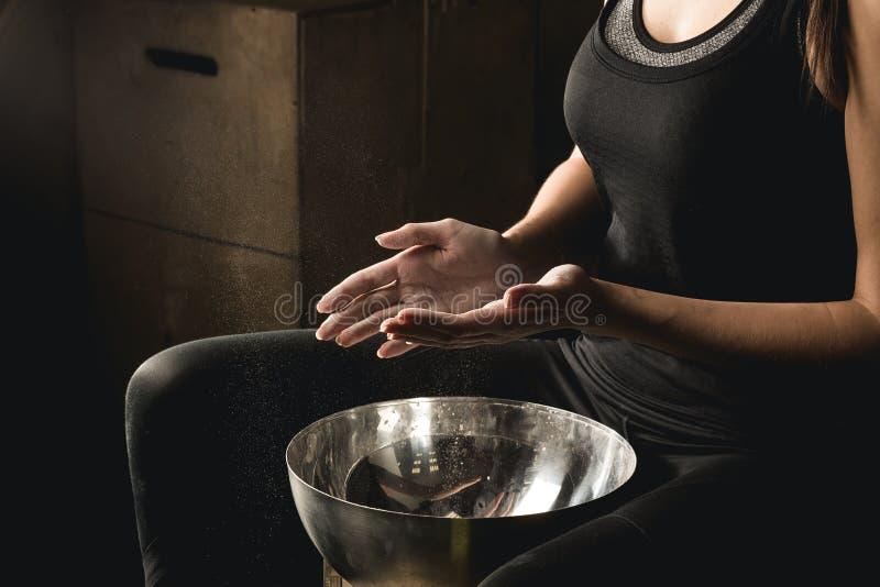 Mujer el aplaudir de manos del carbonato del magnesio de la tiza del gimnasio foto de archivo