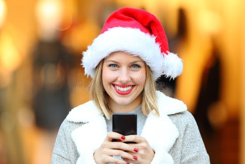 Mujer el los días de fiesta de la Navidad que sostienen el teléfono en la calle foto de archivo