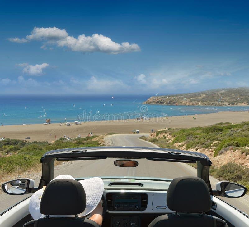 Mujer el vacaciones. contra la perspectiva del mar en el coche foto de archivo