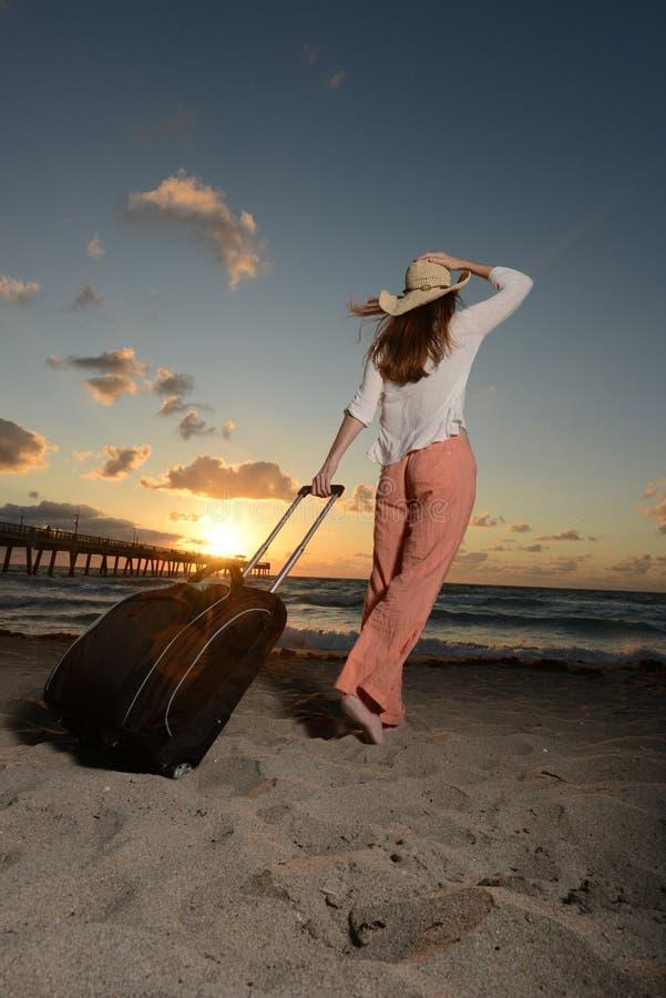 Mujer el vacaciones en el océano durante una salida del sol foto de archivo