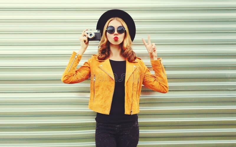 Mujer elegante con cámara retro que saca fotos con chaqueta amarilla, sombrero negro redondo sobre pared de metal fotos de archivo