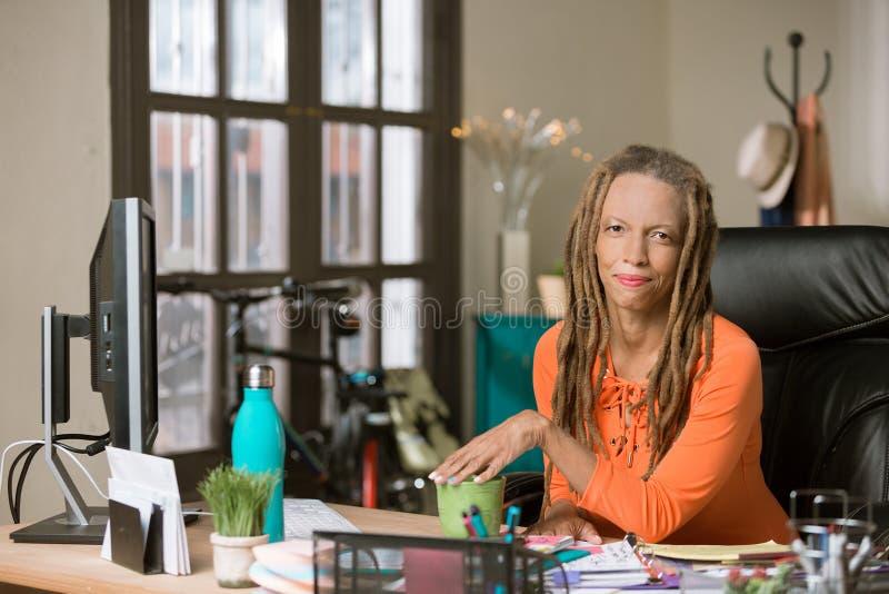 Mujer elegante con Drealocks en una oficina creativa imagen de archivo libre de regalías
