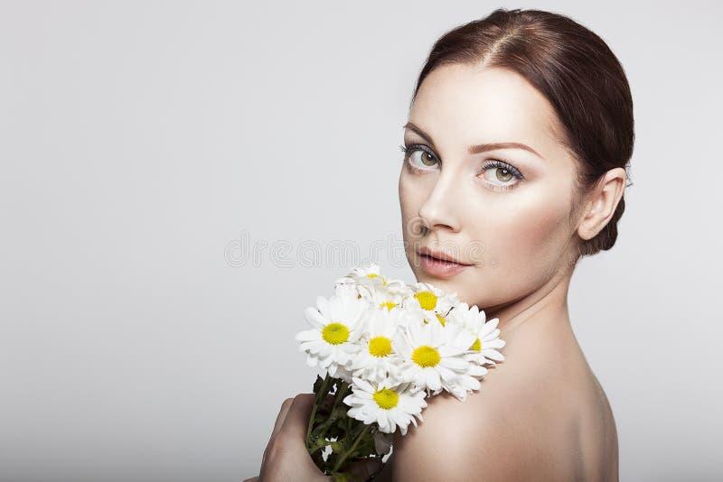 Mujer elegante con las flores de la manzanilla imagen de archivo