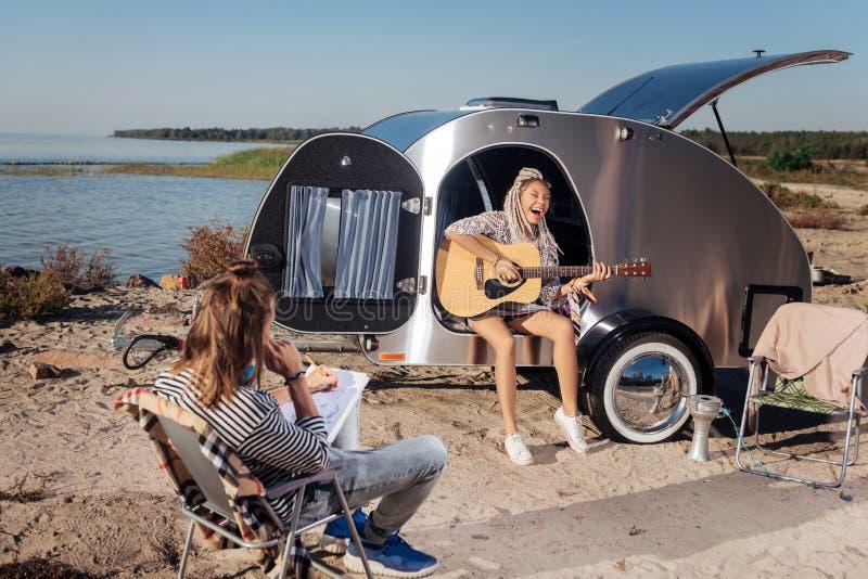 Mujer elegante con los dreadlocks blancos que sostienen la guitarra mientras que juega música fotografía de archivo