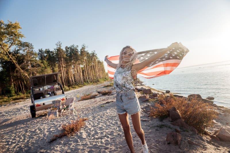 Mujer elegante con los dreadlocks que llevan las gafas de sol que sostienen la bandera americana fotografía de archivo