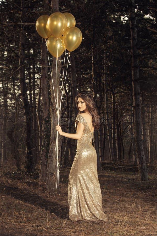 Mujer elegante con los globos en madera foto de archivo
