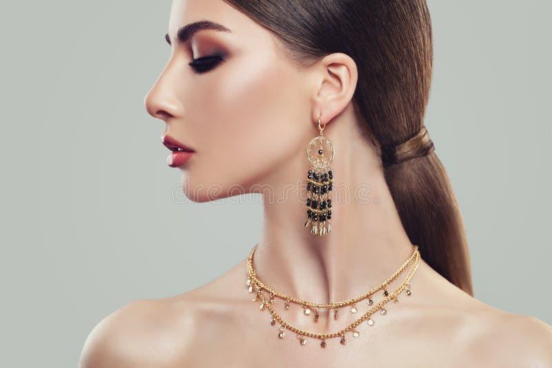 Mujer elegante con los pendientes y la cadena de la joyería del oro foto de archivo libre de regalías