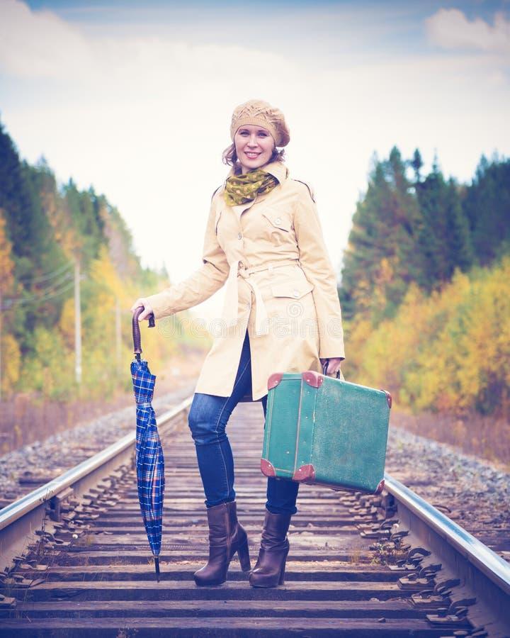 Mujer elegante con una maleta que viaja por el carril imagen de archivo