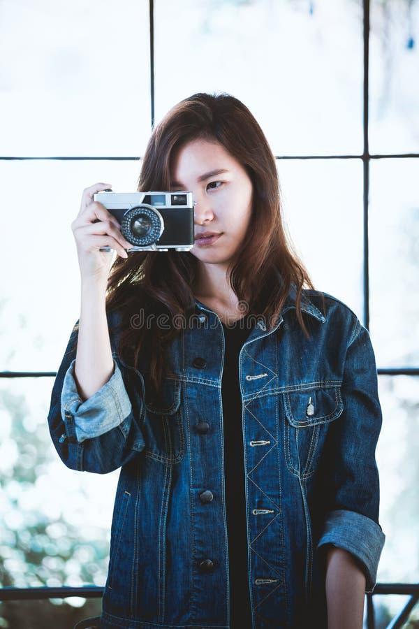 Mujer elegante de la belleza de Asia con una cámara retra en tiempo libre foto de archivo libre de regalías