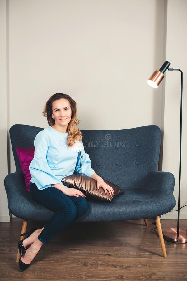 Mujer elegante Mujer de negocios acertada que se sienta en el sofá elegante Empresario de sexo femenino joven sonriente en la ofi foto de archivo libre de regalías