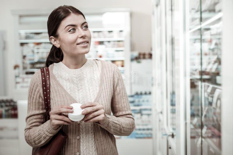 Mujer elegante de ojos verdes que siente curiosa mientras que elige la crema para la piel sensible fotos de archivo libres de regalías