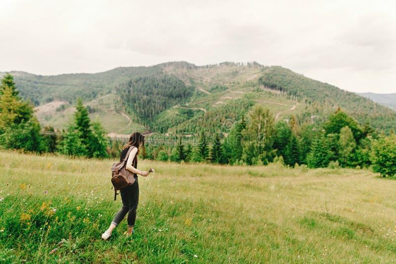 Mujer elegante del inconformista con la mochila que recolecta wildflowers en el mou imagenes de archivo