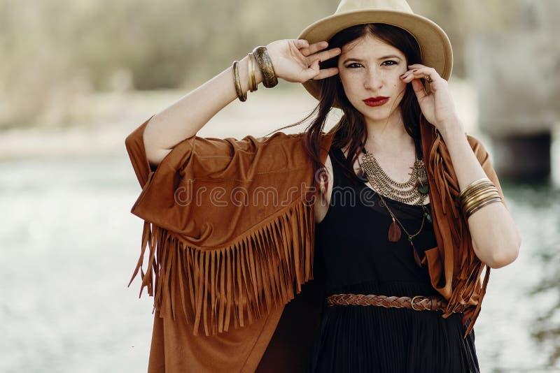 Mujer elegante del inconformista que presenta en sombrero con el pelo ventoso, en la franja p fotos de archivo