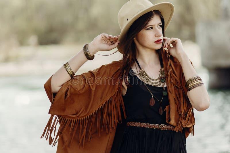 Mujer elegante del inconformista que presenta en sombrero con el pelo ventoso, en la franja p foto de archivo
