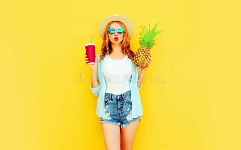Mujer elegante del retrato que envía beso dulce del aire con la piña, taza de jugo en el sombrero de paja del verano, gafas de so foto de archivo