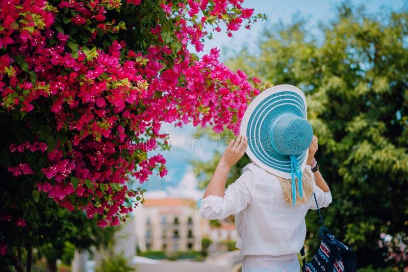 Mujer elegante del viajero con el sombrero de paja que huele las flores coloridas hermosas en las islas de Grecia durante tiempo  fotografía de archivo libre de regalías