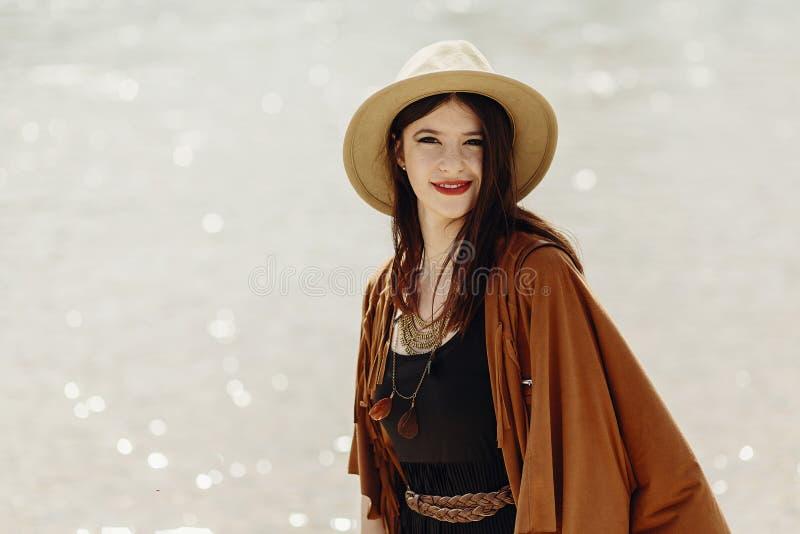 Mujer elegante del viajero del boho en el sombrero, poncho de la franja que presenta cerca de wa imagenes de archivo
