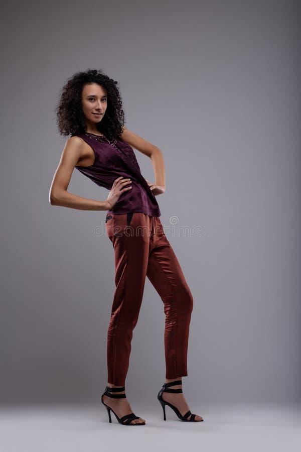 Mujer elegante delgada atractiva con el pelo rizado oscuro imágenes de archivo libres de regalías