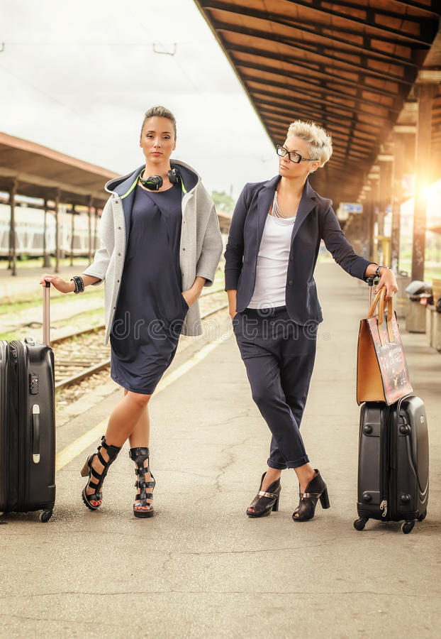 Mujer elegante dos con la maleta que presenta en el ferrocarril imágenes de archivo libres de regalías